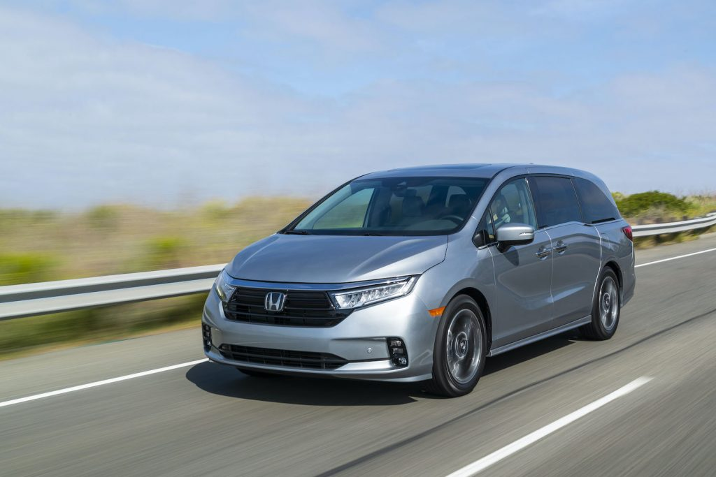 The 2021 Honda Odyssey driving down an empty road