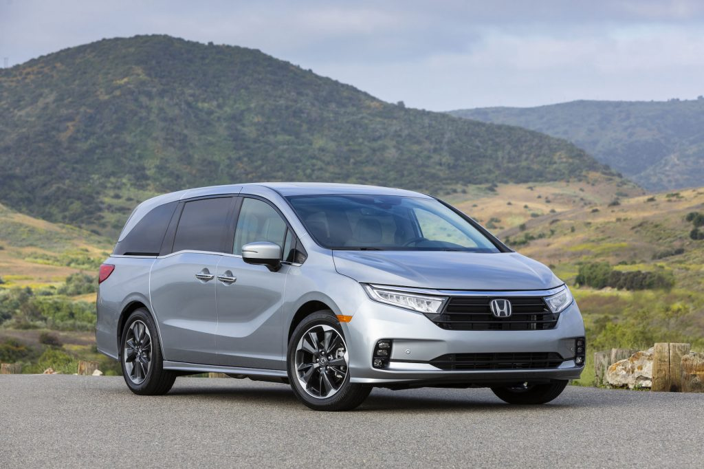 A silver 2021 Honda Odyssey minivan parked in front of grassy hills