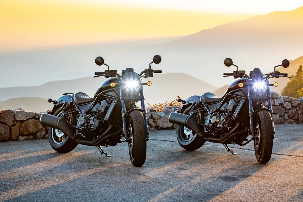 An accessorized black and maroon 2021 Honda Rebel 1100 parked on a mountainside road at sunset