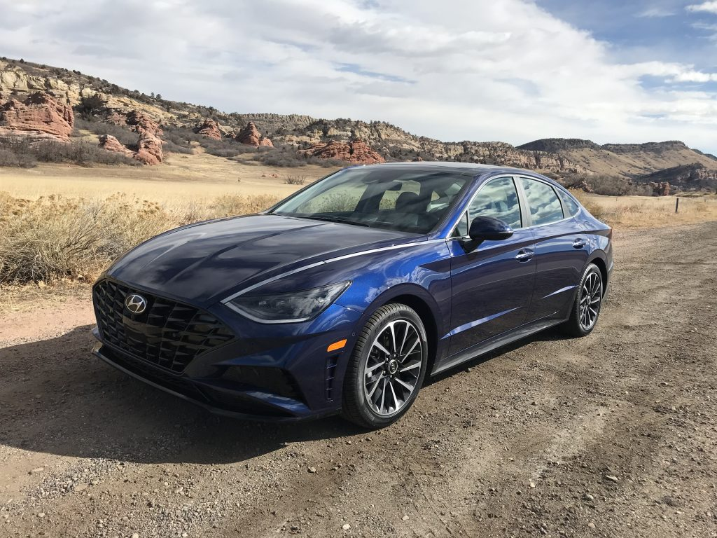 2021 Hyundai Sonata Limited in dark blue parked in the desert with mountains in the background.