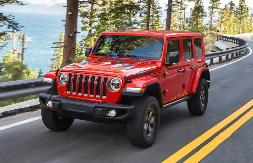 A red 4-door 2021 Jeep Wrangler Rubicon drives on a forest mountain road