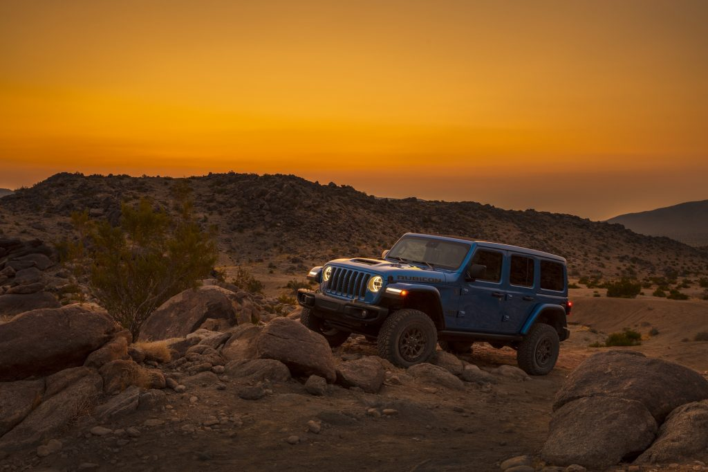 A blue 2021 Jeep Wrangler Rubicon 392 SUV parked on rocks at sunset in mountainous terrain