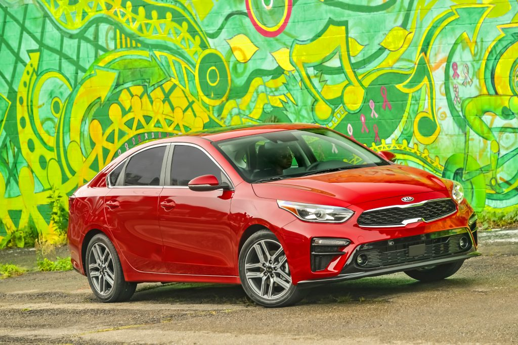 A red 2021 Kia Forte parked next to an artsy green wall
