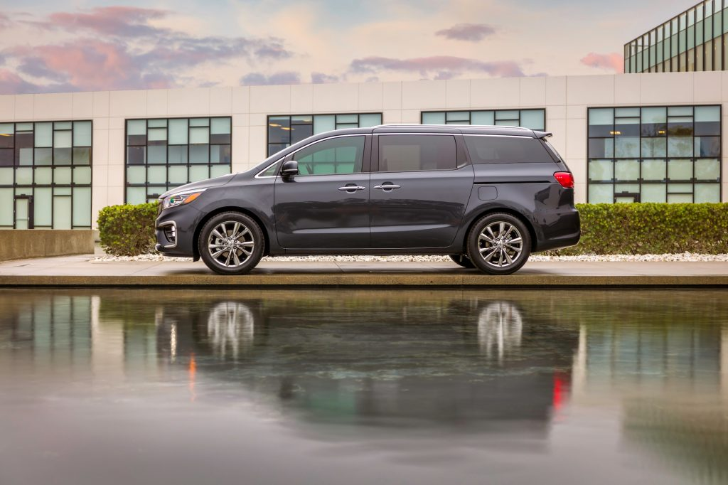 A dark-gray 2021 Kia Sedona parked between a body of water and a low-slung modern building