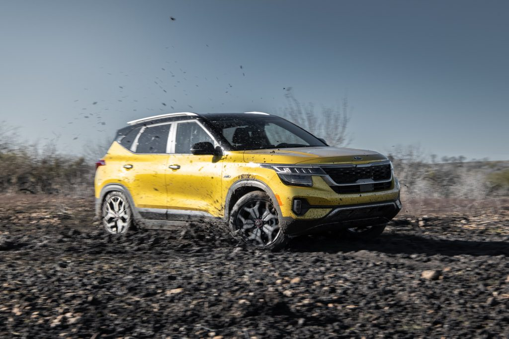 A yellow 2021 Kia Seltos all-wheel-drive compact SUV drives through the mud on a sunny day