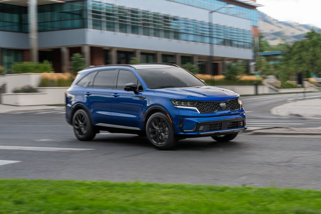 A blue 2021 Kia Sorento SX on display in a parking lot with a building in the background