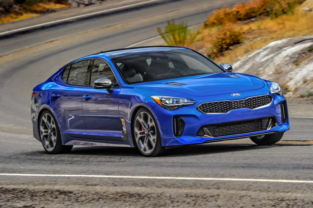 A blue 2021 Kia Stinger GT2 AWD driving down a highway road