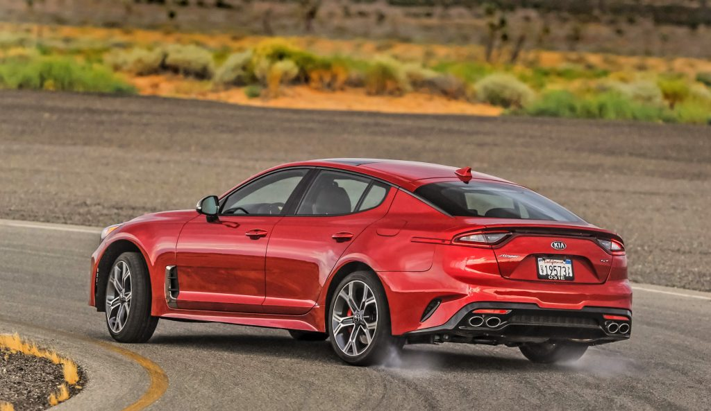A red 2021 Kia Stinger GT2 driving down a race track