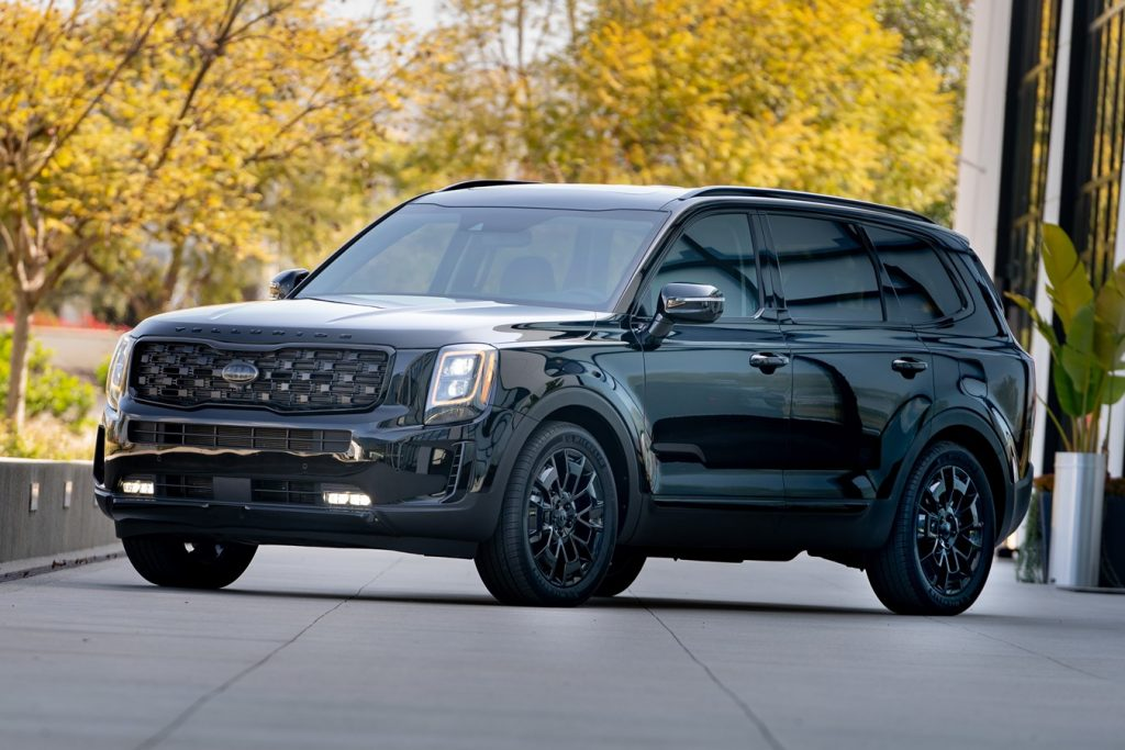 A black 2021 Kia Telluride parked in front of trees