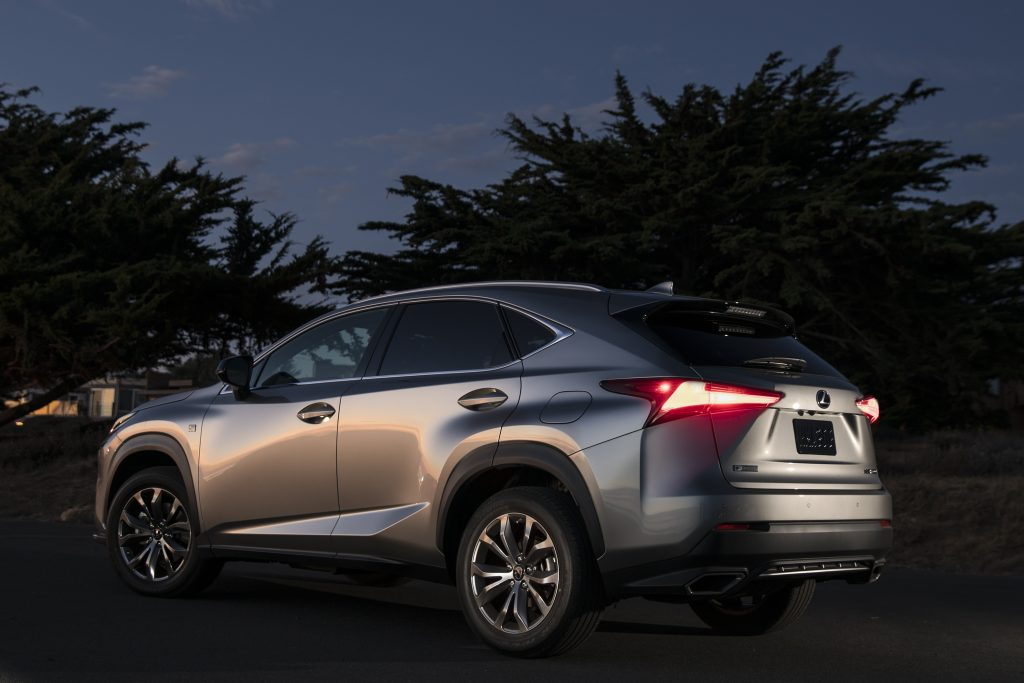 A silver 2021 Lexus NX 300 parked at night with trees in the background