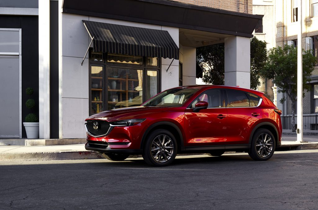 A luxurious red 2021 Mazda CX-5 parked in front of a building