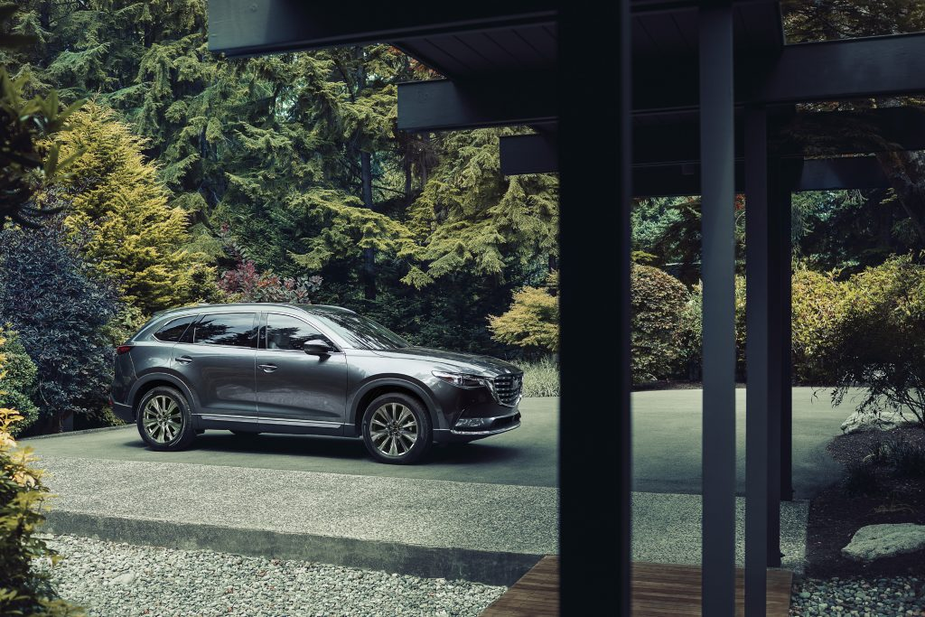 A silver 2021 Mazda CX-9 parked in a driveway with trees in the background