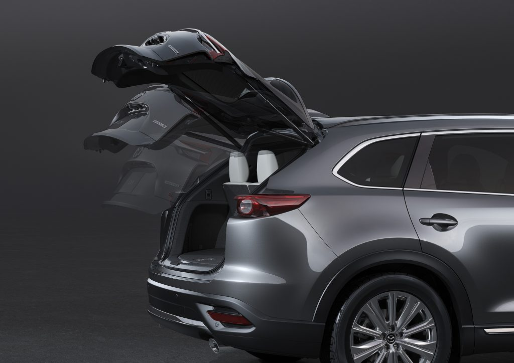 An action shot of a silver 2021 Mazda CX-9's liftgate opening, revealing its small cargo area.