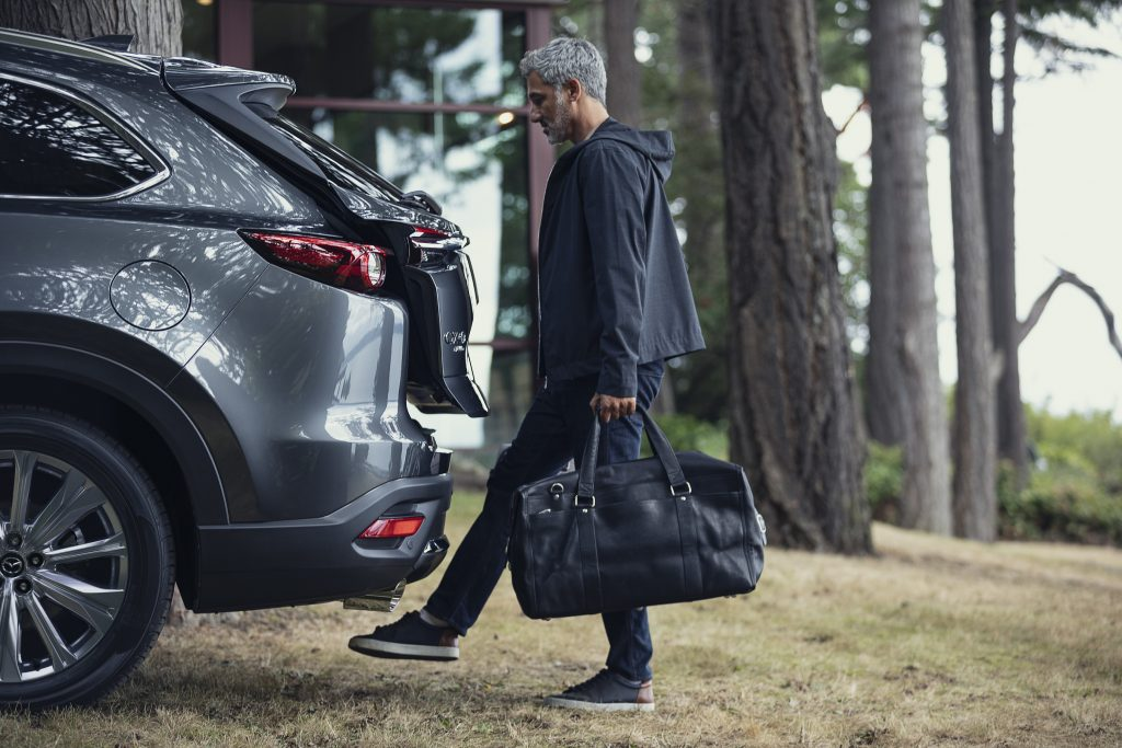 A man getting ready to put a bag in the 2021 Mazda CX-9's cargo area