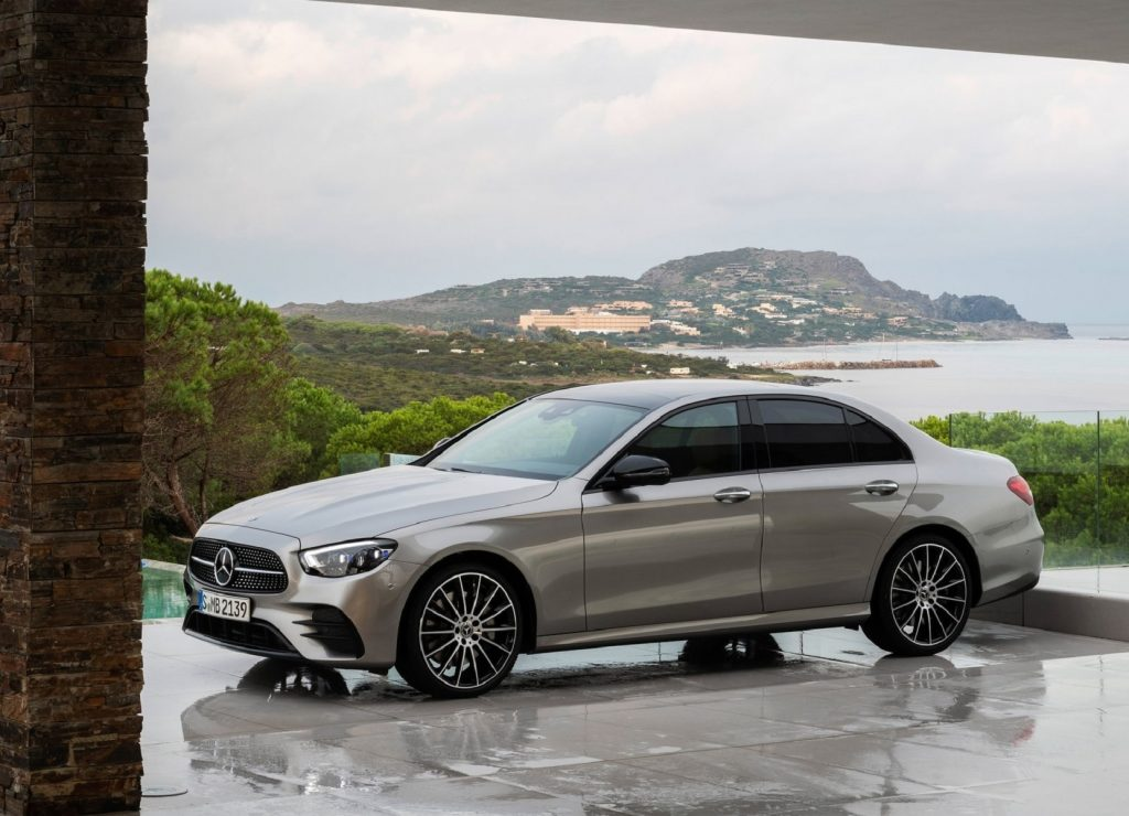 A tan 2021 Mercedes-Benz E-Class on a forested mountain overlooking a bayside city