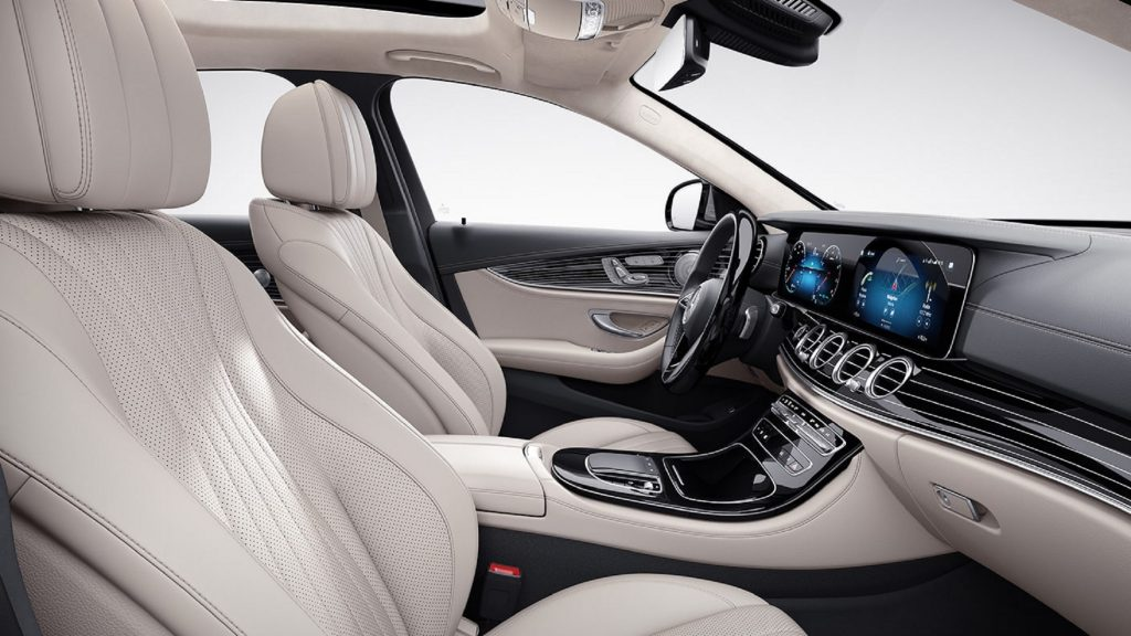 The beige-and-gray-leather front seats and piano-black-wood-trimmed dashboard of the 2021 Mercedes-Benz E450 4MATIC