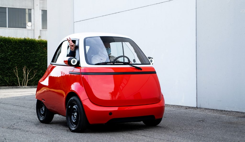 A red-and-white 2021 Microlino 2.0 pre-production prototype with two passengers
