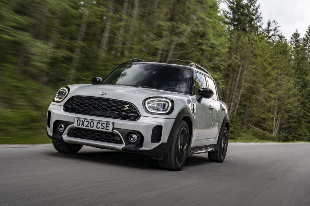 A white 2021 Mini Cooper Countryman travels on a road lined by pine trees on a cloudy day