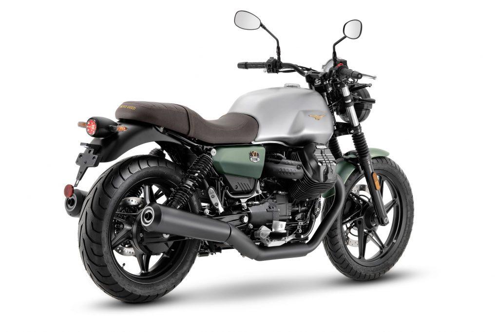 The rear 3/4 view of the silver-and-green 2021 Moto Guzzi V7 Stone Centenario