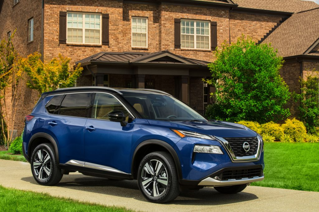 A blue 2021 Nissan Rogue parked in front of a house