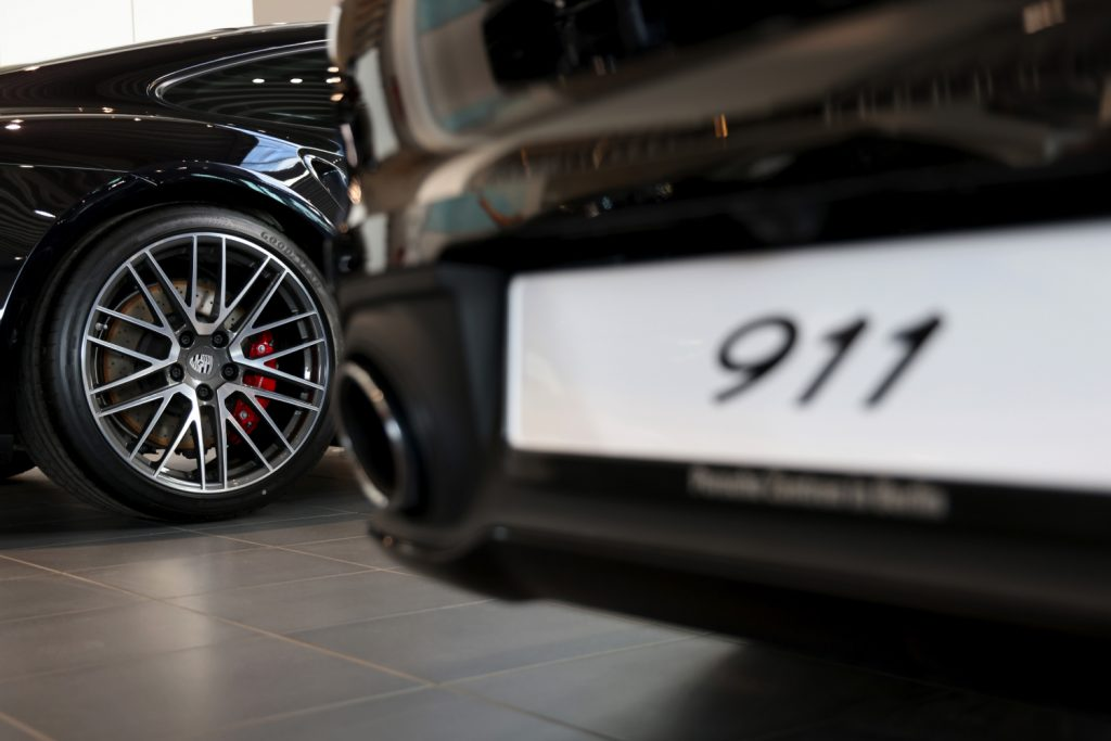 Two black 2021 Porsche 911 cars on display in a showroom