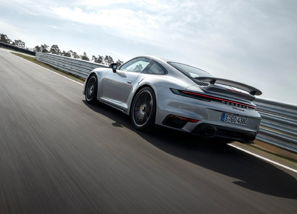 The rear 3/4 view of a silver 2021 Porsche 911 Turbo S driving around a racetrack corner