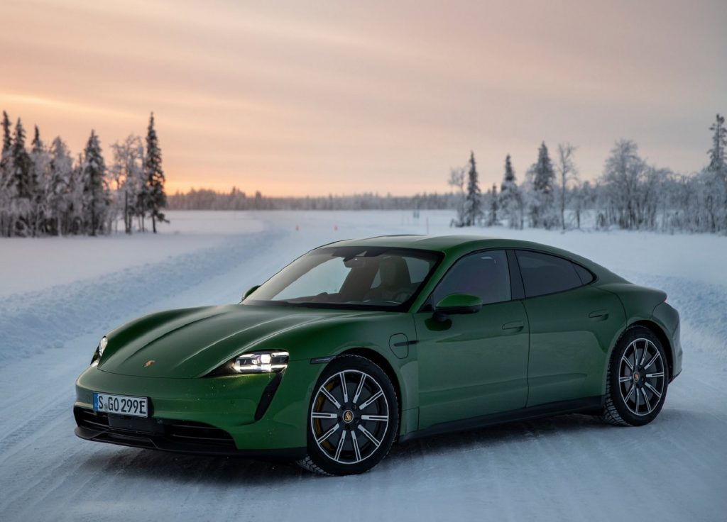 A green 2021 Porsche Taycan 4S in a snow-covered forest