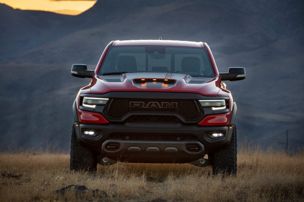 A red 2021 Ram 1500 TRX parked in a field of dry weeds in front of mountains at dusk