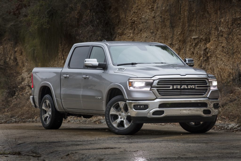 A silver 2021 Ram 1500 Laramie pickup truck parked on wet asphalt at the foot of a cliff