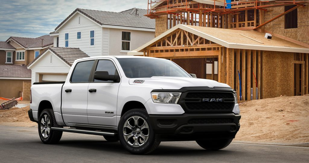 A white 2021 Ram 1500 Tradesman HFE EcoDiesel parked on the street outside a house under construction
