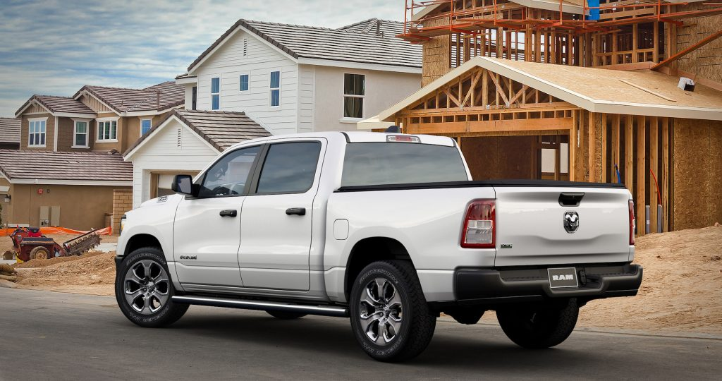 A white 2021 Ram 1500 Tradesman HFE EcoDiesel crew cab pickup truck parked outside a house under construction