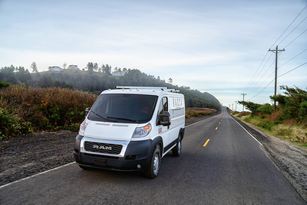 A white 2021 Ram ProMaster van on a rural two-lane road