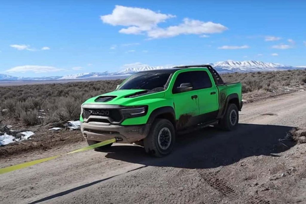 lime-green Ram TRX getting  pulled off the trail after a break down