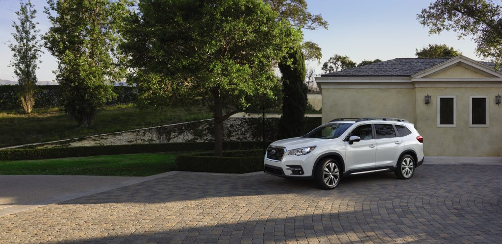 A white 2021 Subaru Ascent parked in the drive way in front of a house