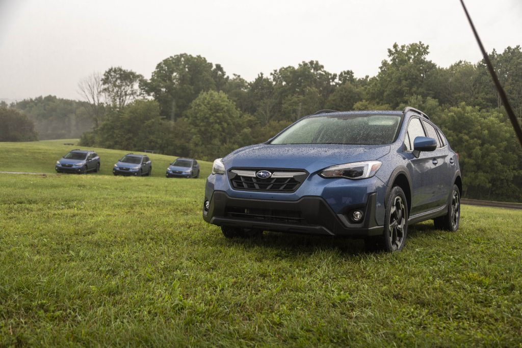 A blue 2021 Subaru Crosstrek Limited parked in the grass for a photoshoot with 3 other Subarus in the far-off distance