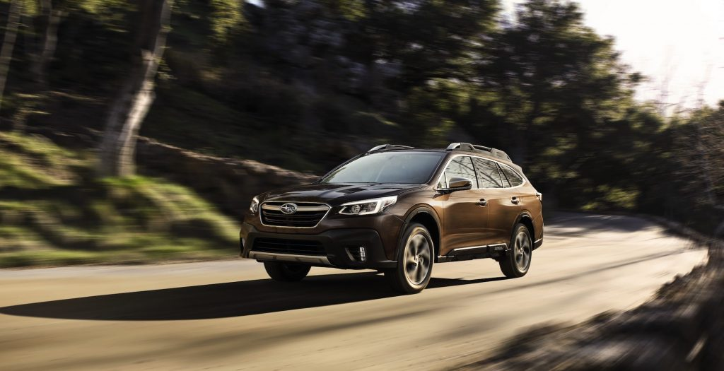 A brown 2021 Subaru Outback travels on a rural road flanked by trees and green hills