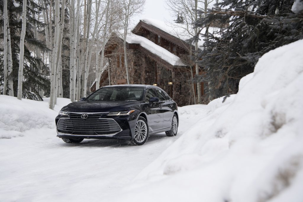 A dark-blue 2021 Toyota Avalon Limited AWD parked in the snow outside a modern cabin in the woods