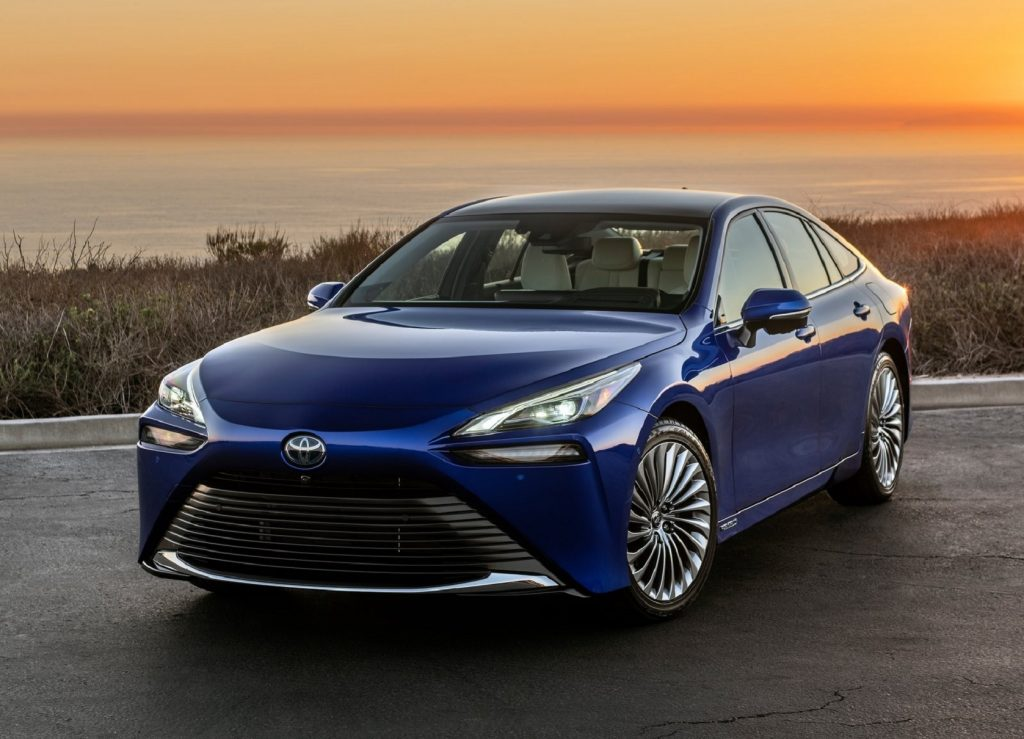 The front 3/4 view of a blue 2021 Toyota Mirai hydrogen fuel-cell electric car by the ocean at sunset