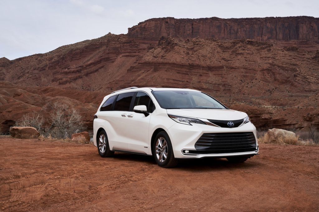 A white 2021 Toyota Sienna Limited minivan parked on red dirt in front of a butte