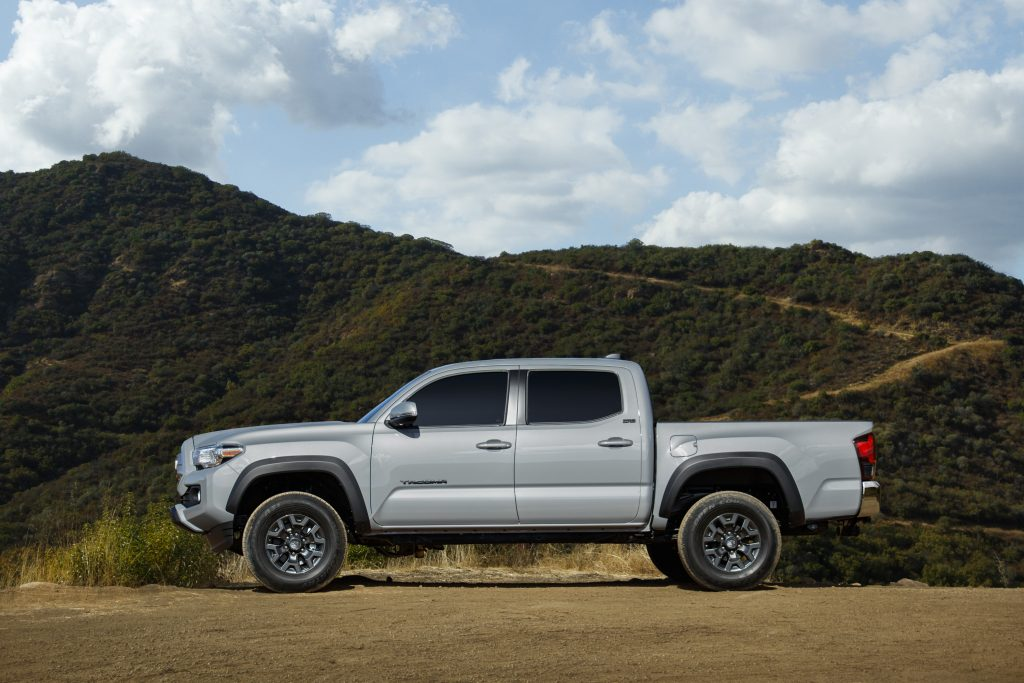 A silver 2021 Toyota Tacoma Trail Edition on display in front of a mountain range