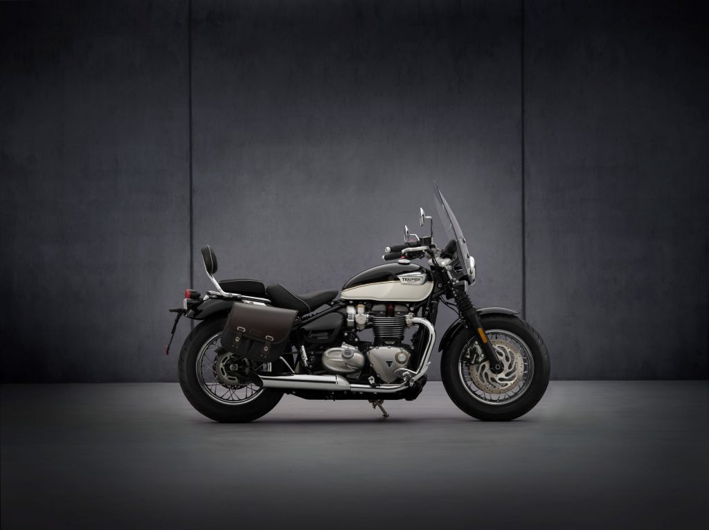 The side view of a black-and-white 2021 Triumph Bonneville Speedmaster with black saddlebags and a windscreen