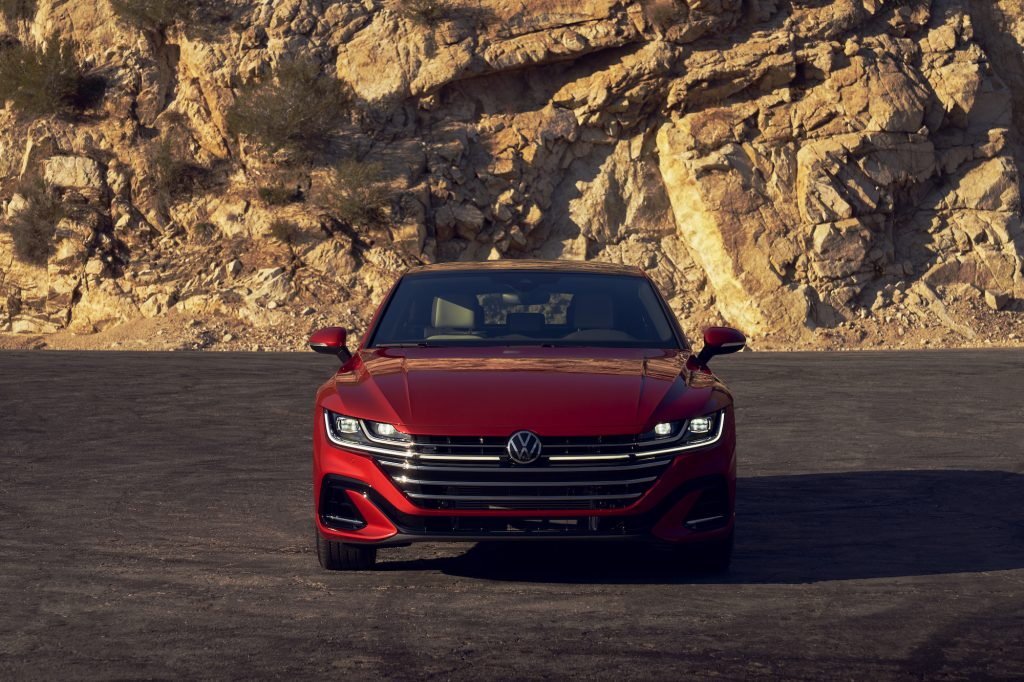 Front view of a red 2021 Volkswagen Arteon with its lights on, parked on a slab of asphalt in front of a rocky mountain