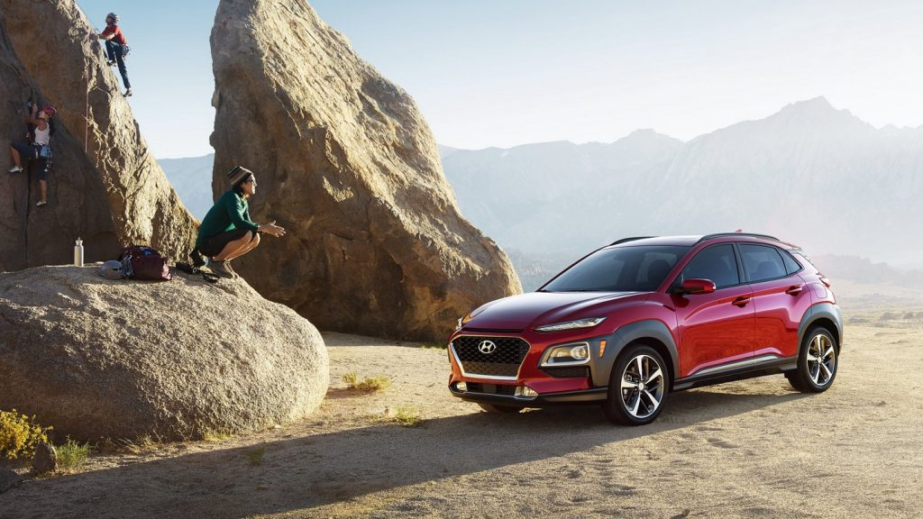 A red 2021 Hyundai Kona parked on the edge of a rocky cliff