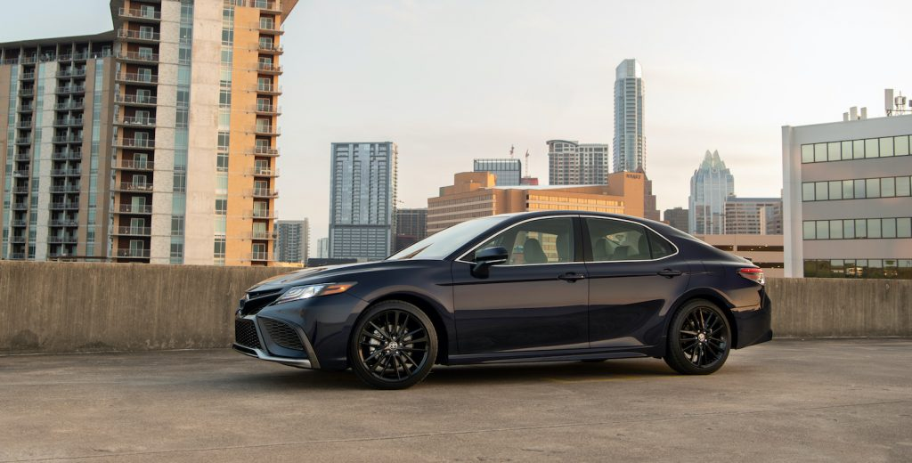 The Toyota Camry parked in front of a city skyline