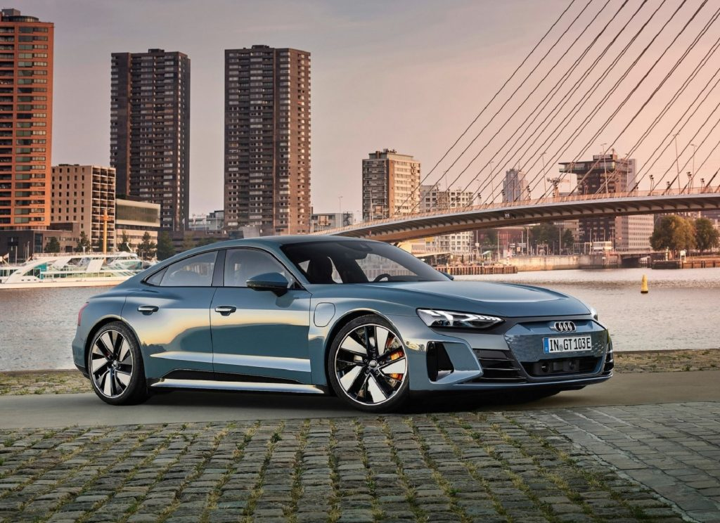 A blue-gray 2022 Audi E-Tron GT Quattro by a bayside city at sunset