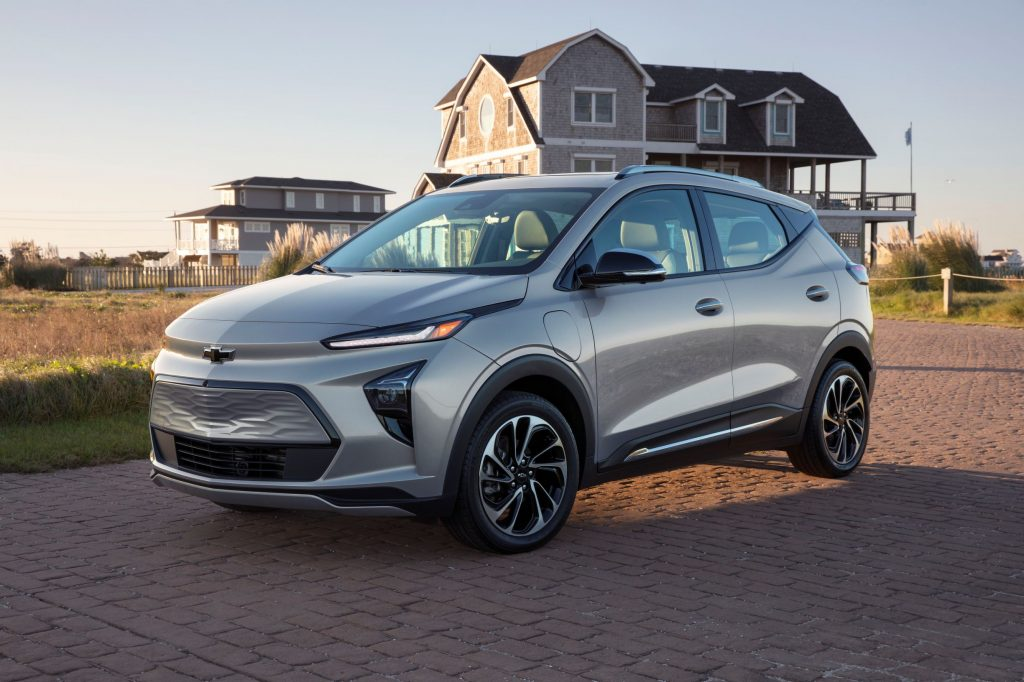 A silver 2022 Chevrolet Bolt EUV by a beach house at sunset