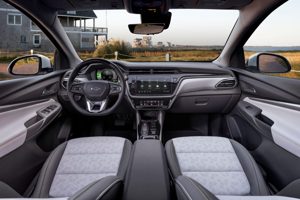 The gray-and-black front seats and dashboard of the 2022 Chevrolet Bolt EUV while it's parked on a beach