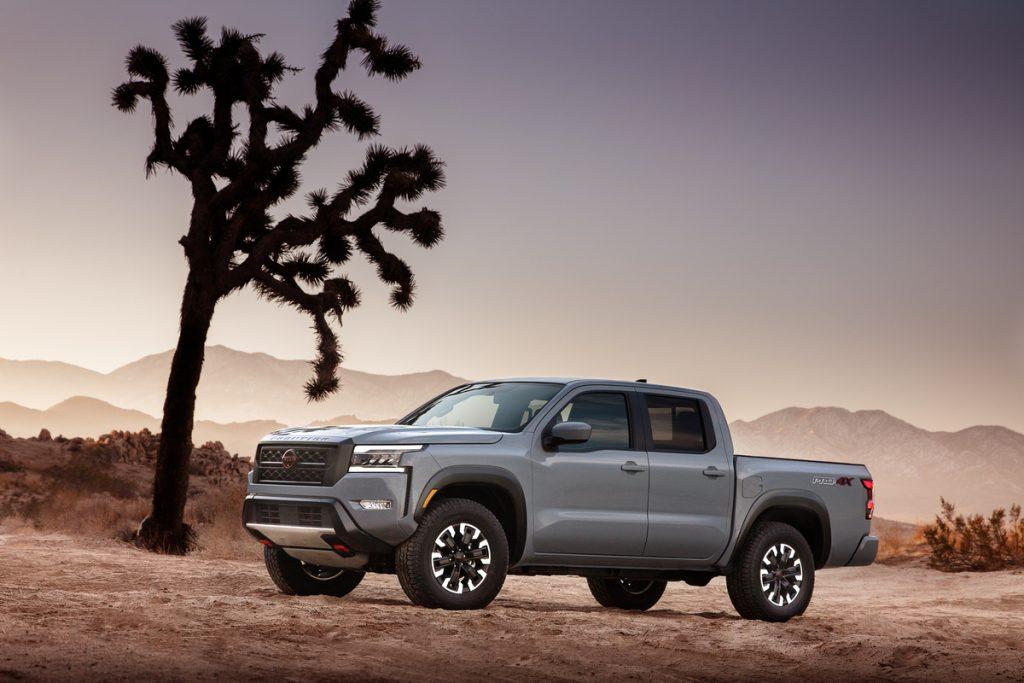 A light gray 2022 Nissan Frontier, a midsize truck, sits beside a tree among a rugged dessert