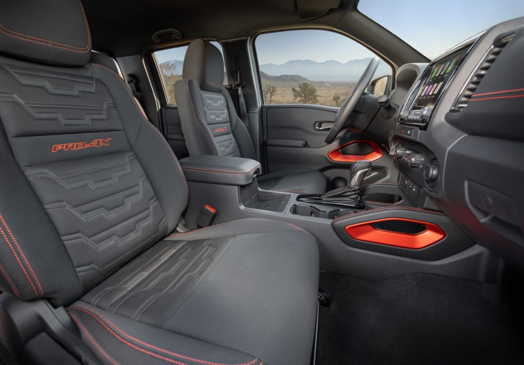 An interior shot of the 2022 Nissan Frontier showing off detailed dark-gray cloth seats with vibrant orange stitching