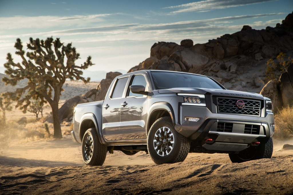 A gray 2022 Nissan Frontier sits parked among a rugged dessert terrain